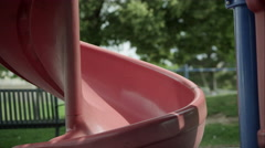 Slow motion of red headed girl coming down slide and smiling. Stock Footage