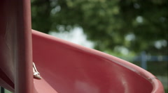 Up close slow motion of red headed girl coming down slide in park. Stock Footage