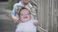 Slow motion rack focus of young boy holding up baby photo of himself with cleft Stock Footage