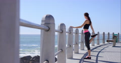 Athletic woman stretching on promenade before running - stock footage