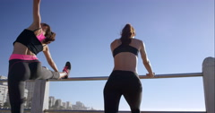 Two athletic friends stretching on promenade before run - stock footage