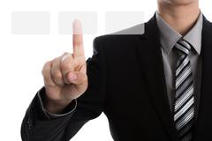 Business man touching an imaginary screen against white background Stock Photos