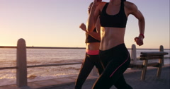 Two athletic woman running outdoors slow motion on promenade at sunset near Stock Footage