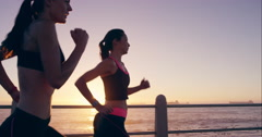 Two athletic woman running outdoors slow motion on promenade at sunset near - stock footage