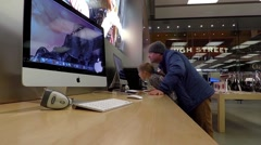Father and daughter playing new macbook inside Apple store - stock footage