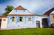 Stock Photo of Viscri, Romania - June 23, 2013: Blue painted traditional house with green sh