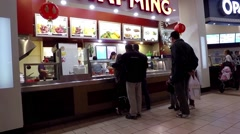 Couple buying food at food court inside Coquitlam center mall Stock Footage