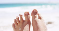 Close up of sandy feet wiggling toes on tropical beach vacation - stock footage