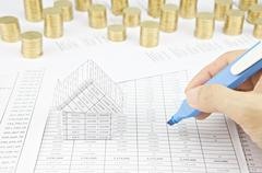 Man is auditing account by highlighter beside house Stock Photos