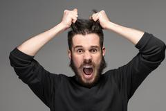 frustration, man tearing hair out in anger - stock photo