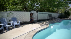 Slow motion of 3 girls coming in through gate next to pool. Stock Footage