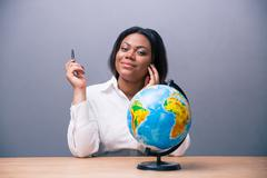 Businesswoman sitting at the table with pen and globe - stock photo