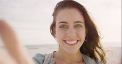 Beautiful woman taking selfie using phone on beach at sunset smiling and Stock Footage