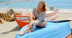 Woman in Sweater Sitting on Blue Platform at Beach Stock Footage