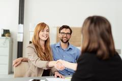Happy young couple meeting with a broker - stock photo