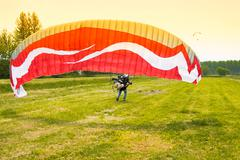 man with motorized paraglider takes off from a field - stock photo