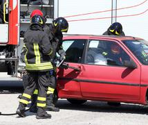 Firefighter opens car door with pneumatic shears after the road accident - stock photo