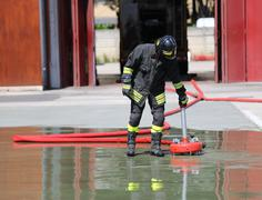 Firefighter positions a powerful fire hydrant Kuvituskuvat
