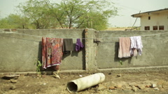 Laundry hanging to dry on wall, long shot Stock Footage