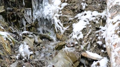 Mountain brook flows on stony snowy soil with icicles and ice Stock Footage