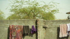 Carrying water on head behind a wall, long shot, shallow DOF Stock Footage