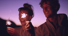 Friends on the beach with sparkers celebrating at sunset Stock Footage