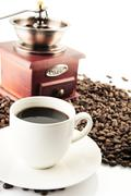 Coffee cups and saucer and winnower on white - stock photo
