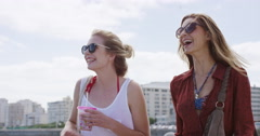 Two girls woman friends sharing drink walking on promenade of seaside town Stock Footage