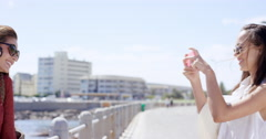 Group of Teenage girls taking photo using mobile phone at beach on summer Stock Footage