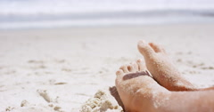 Close up of sandy feet wiggling toes two beautiful young woman sitting on - stock footage