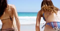 Rear view beautiful young woman wiping beach sand off ass wearing string bikini Stock Footage