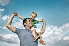 Son seating on the father under beautiful sky with sun Stock Photos