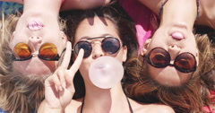 Top view of three teeanage girl friends lying on back blowing bubblegum candy - stock footage