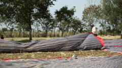 Indian man spreading fabric for a festival, long shot, shallow DOF Stock Footage