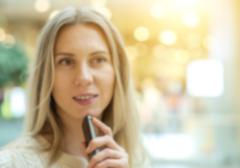 Stock Photo of Women using mobile phone on the bokeh background