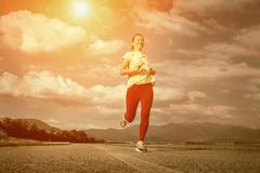 Beautiful female running on road under sky with sun light - stock photo