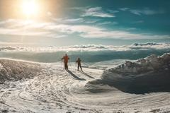 Stock Photo of Two skiers on the peak of mountain in sunny day.