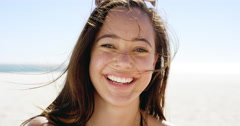 Close up portrait of beautiful young woman smiling on tropical beach slow motion Stock Footage