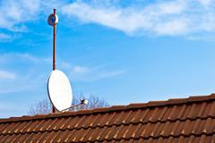 Satellite dish on the red roof Stock Photos