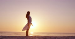 Free happy woman arms outstretched enjoying nature on beach at sunset face Stock Footage