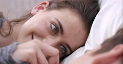 Attractive young couple making out in bed smiling engaged in foreplay touching - stock footage