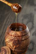 Maple honey flowing from dipper to pot, rustic Stock Photos