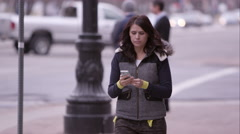 Close view of woman walking down the sidewalk answering call on cell phone. Stock Footage