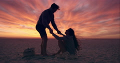 Happy couple walking towards sunset on empty beach dramatic orange sky in Stock Footage