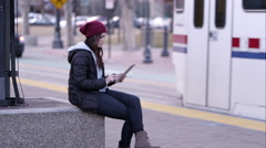 Woman using tablet as transit train pulls to a stop. - stock footage