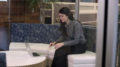Woman using laptop then stops to interact with person. - stock footage