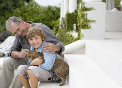 Older man and grandson petting cat on steps Stock Photos