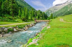 Mountain stream and high peaks of Austrian Alps Stock Photos