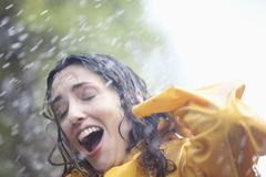 Rain falling on surprised woman - stock photo