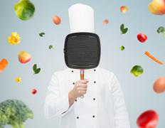 male chef cook covering face with grill pan - stock photo
